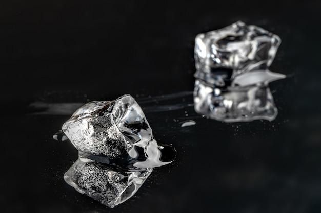 Cubetti di ghiaccio di fusione su priorità bassa nera, fine in su