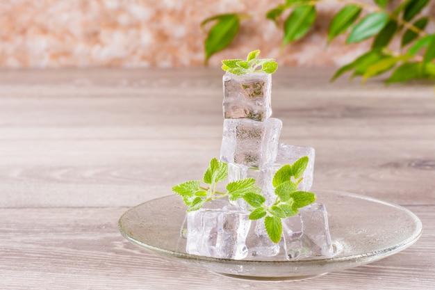 Cubetti di ghiaccio e foglie di menta di fusione su un piattino su una tavola di legno