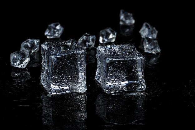 Cubetti di ghiaccio su fondo di vetro isolato nero