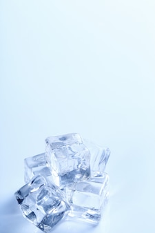 Cubetti di ghiaccio sulla tavola bianca con copyspace