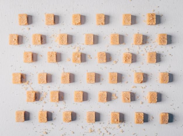 Cubetti di zucchero di canna allineati. disteso.
