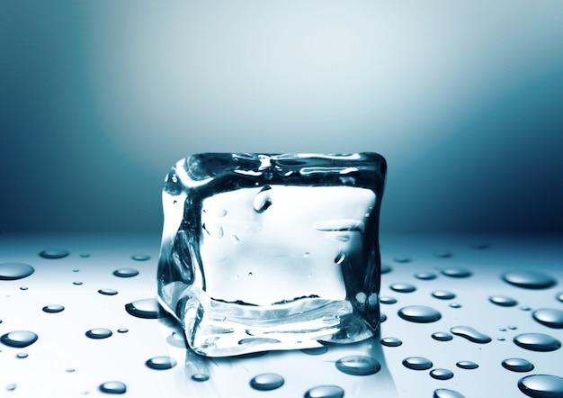 Cubetto di ghiaccio con gocce d'acqua isolato su sfondo blu brillante