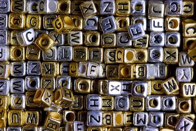 Cubi d'oro e d'argento con il primo piano delle lettere inglesi nere.