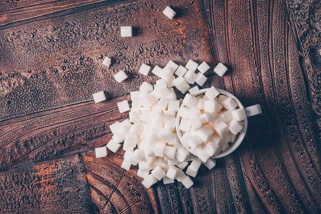 Cubi dello zucchero bianco di disposizione piana in tazza sulla tavola di legno scura. orizzontale