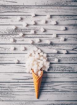 Cubi dello zucchero bianco di vista superiore nella cialda del gelato sulla tavola di legno bianca. verticale