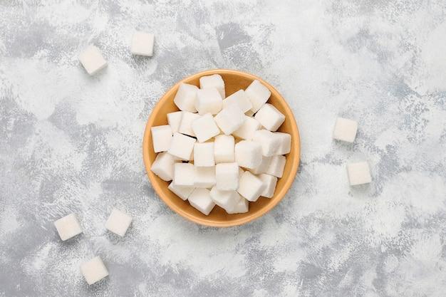 Cubi dello zucchero bianco su calcestruzzo, vista superiore