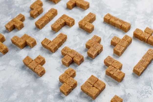 Cubi dello zucchero bruno su calcestruzzo, vista superiore