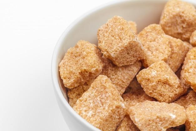 Cubi dello zucchero di canna di brown isolati su bianco