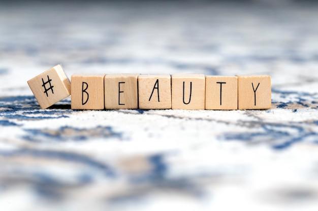 Cubi di legno con un hashtag e la bellezza di parola, fondo di concetto di media sociali