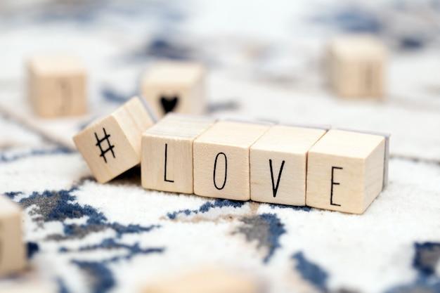 Cubi di legno con un hashtag e la parola amore, social media e sfondo di concetto di san valentino