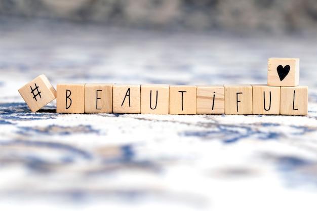 Cubi di legno con un hashtag e la parola bella, fondo sociale di concetto di media