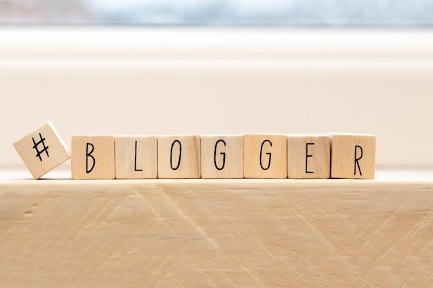 Cubi di legno con un hashtag e la parola blogger, concetto di social media