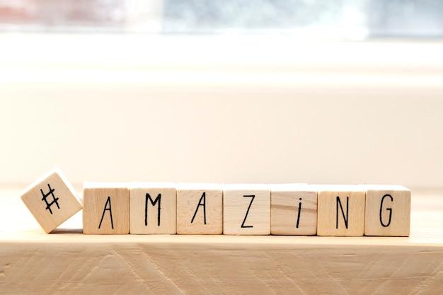 Cubi di legno con un hashtag e la parola stupefacente, concetto di social media