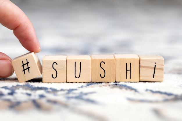 Cubi di legno con un hashtag e la parola sushi, social media e concetto di cibo
