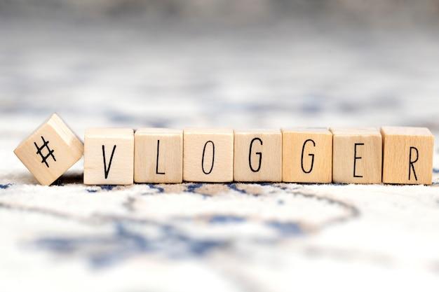 Cubi di legno con un hashtag e la parola vlogger, concetto di social media