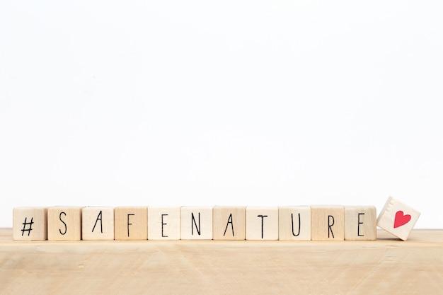 Cubi di legno con un hashtag e le parole safe nature, concetto di social media,