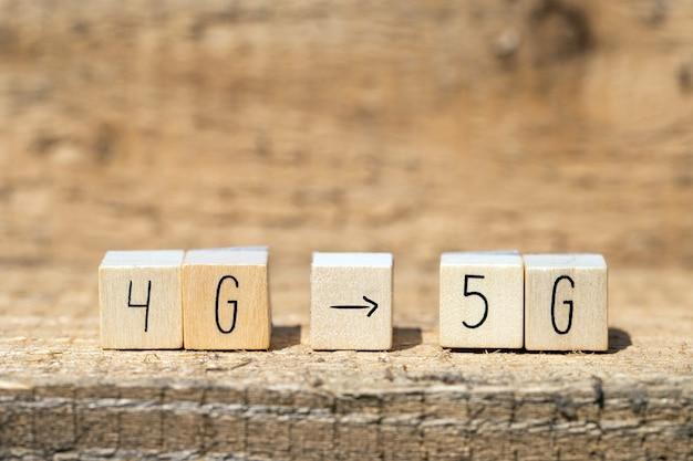 Cubi di legno da 4g a 5g con freccia nera che punta su un tavolo di legno, un mobile o un concetto tecnologico