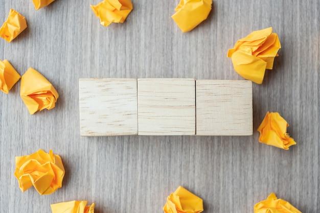 Cubi di legno vuoti con carta sbriciolata sulla tavola di legno