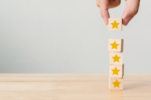Cubo del blocco di legno della costruzione della mano che impila sulla cima con una forma di cinque stelle