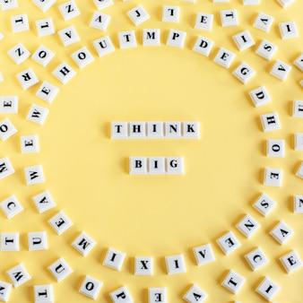 Cubo di blocco di plastica con la parola think big e intorno a singole lettere sparse su sfondo giallo
