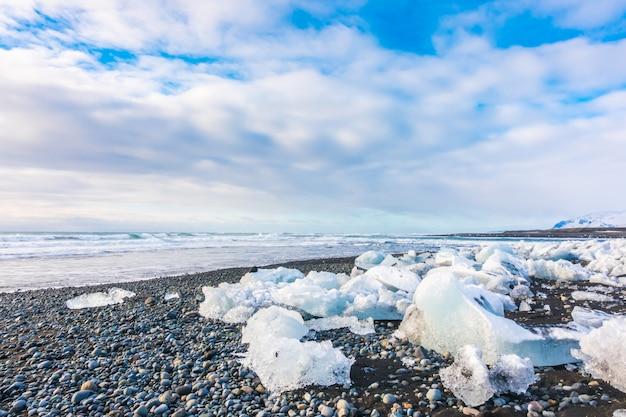Cubo di ghiaccio che rompe sulla spiaggia rocciosa nera, paesaggio di stagione invernale dell'islanda