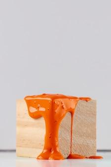 Cubo di legno con vernice arancione gocciolante
