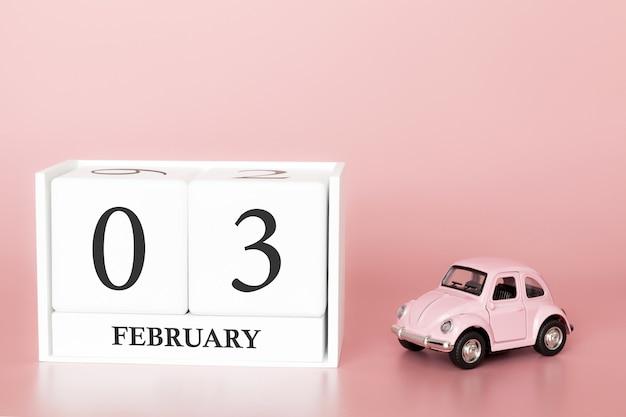 Cubo di legno del primo piano 3 febbraio. 3 ° giorno del mese di febbraio, calendario su una rosa con auto retrò.