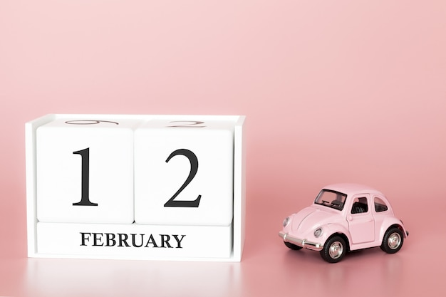 Cubo di legno del primo piano il 12 febbraio. giorno 12 del mese di febbraio, calendario su una rosa con auto retrò.