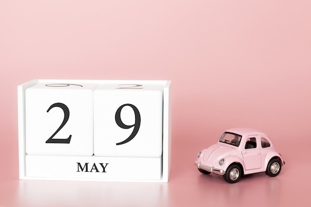 Cubo di legno del primo piano il 29 maggio. giorno 29 maggio mese, calendario su uno sfondo rosa con auto retrò.