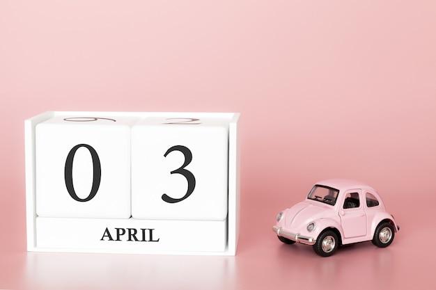 Cubo di legno del primo piano il 3 aprile. 3 ° giorno del mese di aprile, calendario su una rosa con auto retrò.