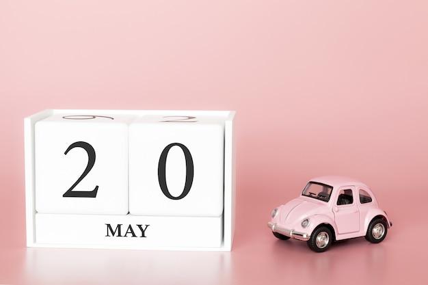 Cubo di legno del primo piano ventesimo maggio. giorno 20 maggio mese, calendario su uno sfondo rosa con auto retrò.