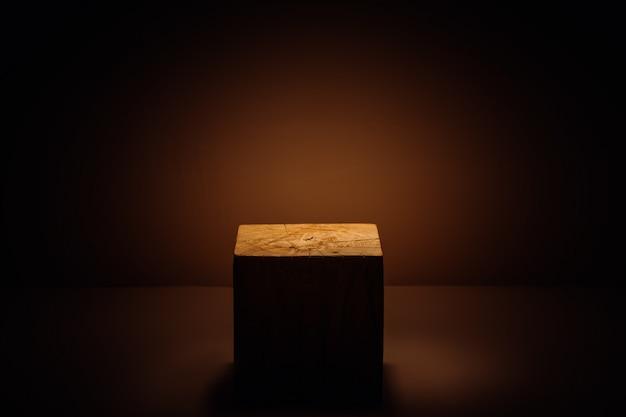 Cubo di legno nel raggio di luce come esposizione del prodotto