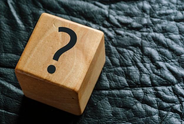 Cubo di legno su pelle nera con punto interrogativo
