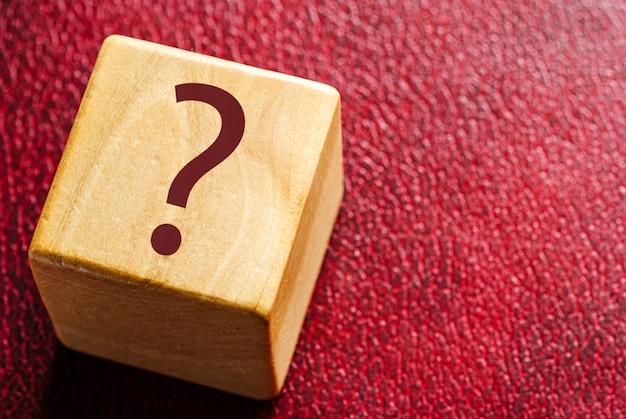 Cubo in legno con punto interrogativo su pelle rossa