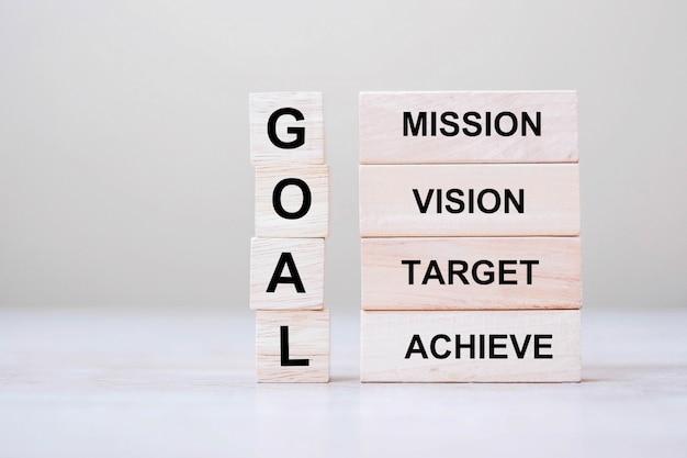 Cubo in legno con testo goal con blocchi mission, vision, target e achieve
