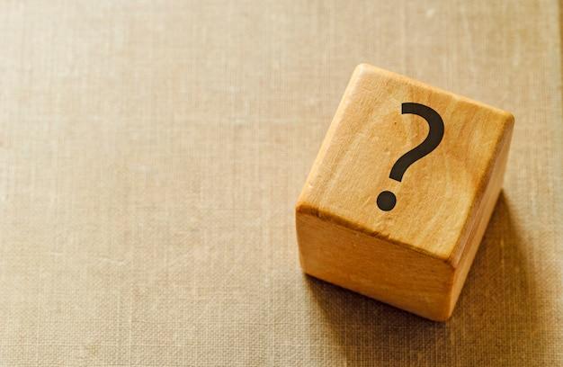 Cubo in legno naturale con punto interrogativo in cima