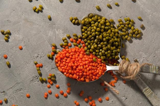 Cucchiai con lenticchie rosse e fagioli verdi su una superficie grigia - super alimento, alimento sano.