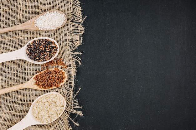Cucchiai con riso assortito su tessuto di lino