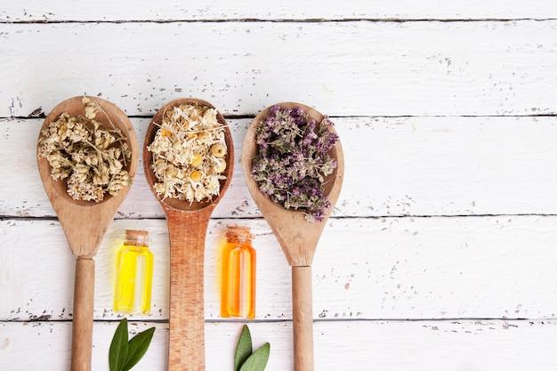 Cucchiai di legno con erbe medicinali essiccate e bottiglie con essenza. tè e tinture medicinali come medicina alternativa