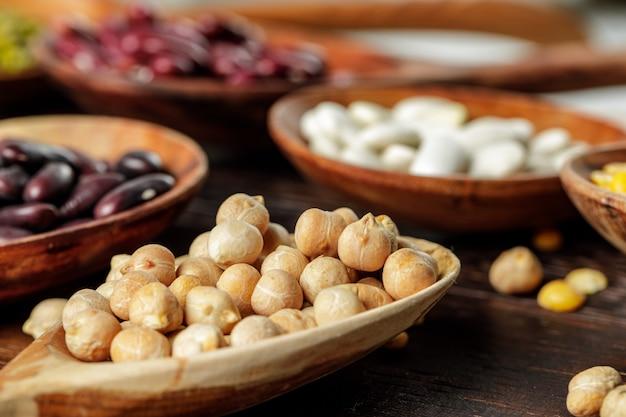 Cucchiai di legno con grani e fagioli sul tavolo di legno