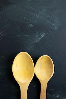 Cucchiai di legno con sfondo nero con texture
