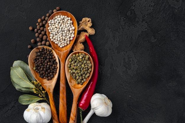 Cucchiai di legno con varie spezie su fondo nero