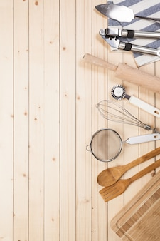 Cucchiai di legno e altri strumenti di cottura con tovaglioli blu sul tavolo della cucina.