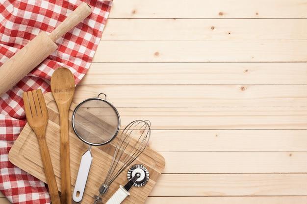 Cucchiai di legno e altri strumenti di cottura con tovaglioli rossi sul tavolo della cucina.