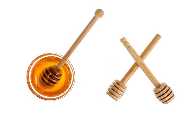 Cucchiai di legno per miele isolati su fondo bianco.