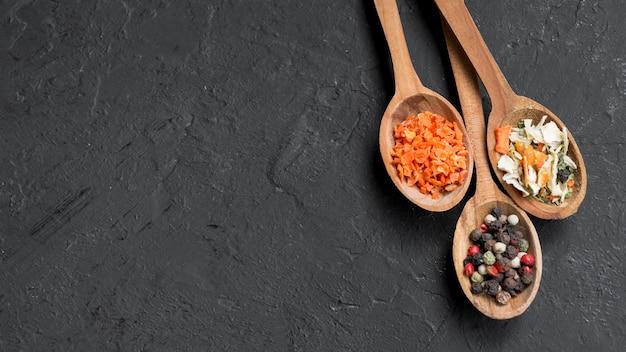 Cucchiai di legno pieni di spezie su sfondo nero