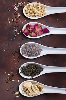 Cucchiai in ceramica con erbe secche, boccioli di fiori e foglie di tè su sfondo di pietra