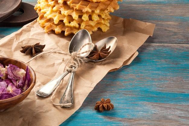Cucchiaini da tè d'annata e petali di rosa su fondo blu di legno