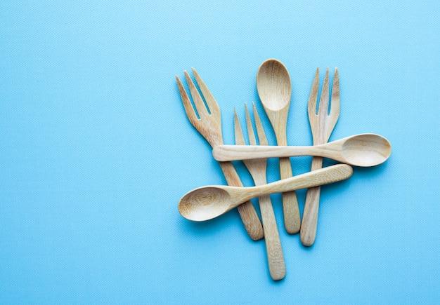Cucchiaino in legno o piccolo cucchiaio e forchetta su sfondo blu.
