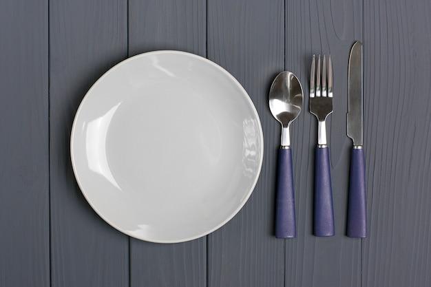 Cucchiaio blu scuro, forchetta, coltello, piatto grigio su un tavolo di legno grigio
